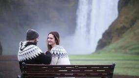 Pares felices jovenes que se sientan en el banco y que toman la foto en smartphone cerca de la cascada de Skogafoss en Islandia