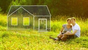 Pares felices jovenes que se sientan en hierba verde en parque y que los sueñan alrededor para poseer la casa Concepto de la hipo libre illustration