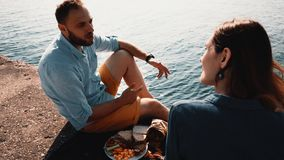 Pares felices jovenes que se sientan en la orilla de un mar y de una consumición Hombre y mujer que tienen comida campestre cerca almacen de video