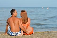 Pares felices jovenes que se sientan en la playa arenosa y el abarcamiento Foto de archivo libre de regalías