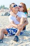 Pares felices jovenes que se sientan en la playa y el abarcamiento del mar Fotografía de archivo libre de regalías