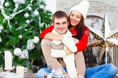 Pares felices jovenes que se sientan por el árbol de Cristmas Imagenes de archivo