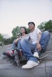Pares felices jovenes que se sientan y que descansan sobre pasos concretos afuera con un monopatín y las cuchillas del rodillo Fotografía de archivo