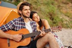 Pares felices jovenes que tocan la guitarra mientras que se sienta en la playa Imagenes de archivo