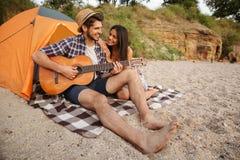 Pares felices jovenes que tocan la guitarra mientras que se sienta en la playa Imagen de archivo
