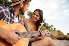 Pares felices jovenes que tocan la guitarra mientras que se sienta en la playa Foto de archivo