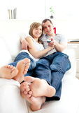 Pares felices jovenes que ven la TV el mentir en el sofá Imagen de archivo libre de regalías