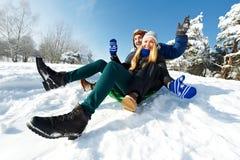 Pares felices jovenes sledding en invierno Foto de archivo libre de regalías