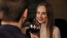 Pares felices jovenes sobre el vidrio de consumición romántico de la fecha de vino rojo almacen de video