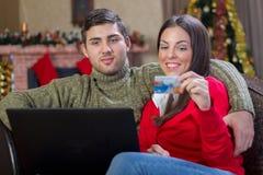 Pares felices jovenes usando E-tienda de la tarjeta de crédito en nig de la Navidad Imagen de archivo