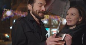 Pares felices jovenes usando smartphone en la noche