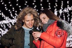 Pares felices jovenes usando smartphone en la noche fotos de archivo