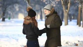 Pares felices juguetones junto durante la vocación de las vacaciones de invierno afuera en parque de la nieve almacen de video