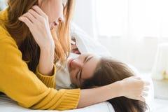 Pares felices lesbianos asiáticos jovenes hermosos de las mujeres LGBT que abrazan y que sonríen mientras que miente junto en cam imágenes de archivo libres de regalías