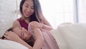 Pares felices lesbianos de las mujeres asiáticas jovenes que despiertan por la mañana en cama en dormitorio en casa almacen de video