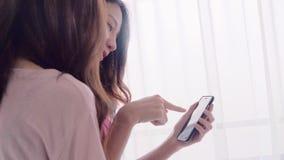 Pares felices lesbianos de las mujeres asiáticas jovenes usando el smartphone que comprueba medios sociales en dormitorio en casa almacen de video