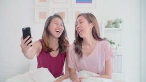 Pares felices lesbianos de las mujeres asiáticas jovenes usando la llamada VIDEO del teléfono con el amigo en dormitorio en casa metrajes