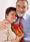 Pares felices mayores con el regalo Foto de archivo libre de regalías
