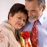 Pares felices mayores con el regalo Imágenes de archivo libres de regalías