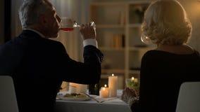 Pares felices mayores que comen la cena y que beben el vino, celebración del aniversario metrajes