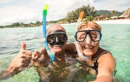 Pares felices mayores que toman el selfie con las máscaras que bucean del equipo de submarinismo foto de archivo