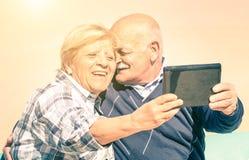 Pares felices mayores que toman un selfie con la tableta moderna Foto de archivo