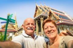 Pares felices mayores que toman un selfie en los templos magníficos del palacio Foto de archivo libre de regalías