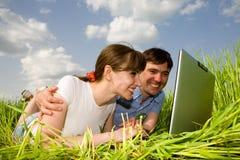 Pares felices ocasionales en el ordenador portátil al aire libre imágenes de archivo libres de regalías