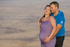 Pares felices, padres futuros, besándose cerca del cráter en la puesta del sol Hombre que abraza a su mujer embarazada Fotos de archivo