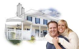 Pares felices que abrazan delante del dibujo y de la foto de la casa en blanco Fotos de archivo libres de regalías