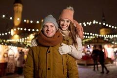 Pares felices que abrazan en el mercado de la Navidad Imagenes de archivo