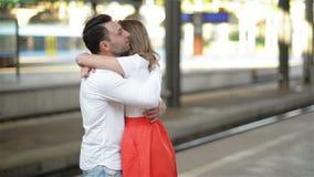 Pares felices que abrazan en la plataforma del ferrocarril Adiós en la estación, la chica joven y Guy Are Hugging On de tren almacen de metraje de vídeo