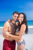 Pares felices que abrazan en la playa y que miran la cámara Imágenes de archivo libres de regalías
