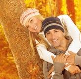 Pares felices que abrazan en parque del otoño Imagenes de archivo