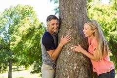Pares felices que abrazan un árbol Fotografía de archivo