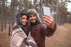 Pares felices que abrazan y que hacen selfiee en un bosque frío al aire libre imagen de archivo libre de regalías