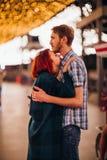 Pares felices que abrazan y que besan por la tarde en las guirnaldas ligeras imágenes de archivo libres de regalías