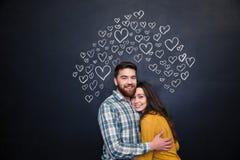 Pares felices que abrazan y que se colocan sobre tablero negro Imagen de archivo