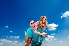 Pares felices que abrazan y que se divierten debajo del cielo azul Foto de archivo