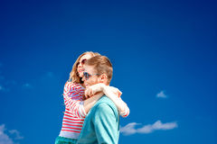 Pares felices que abrazan y que se divierten debajo del cielo azul Foto de archivo libre de regalías