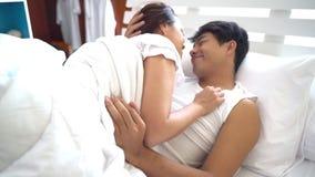 Pares felices que abrazan y que se acurrucan en cama almacen de video