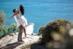 Pares felices que abrazan y que se besan, paisaje marino hermoso del behinde de un mar mediterrianean en Grecia foto de archivo libre de regalías