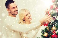 Pares felices que adornan el árbol de navidad en casa Fotos de archivo libres de regalías