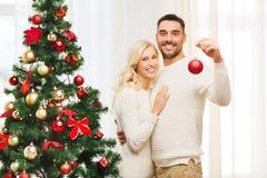 Pares felices que adornan el árbol de navidad en casa Fotos de archivo