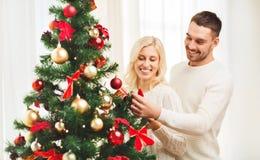 Pares felices que adornan el árbol de navidad en casa Imagen de archivo libre de regalías