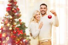 Pares felices que adornan el árbol de navidad en casa Imágenes de archivo libres de regalías