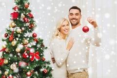Pares felices que adornan el árbol de navidad en casa Fotografía de archivo libre de regalías