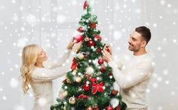 Pares felices que adornan el árbol de navidad en casa Imagenes de archivo