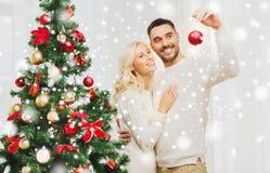 Pares felices que adornan el árbol de navidad en casa Foto de archivo libre de regalías