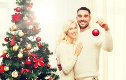 Pares felices que adornan el árbol de navidad en casa Imagen de archivo